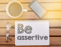 Notebook on table with text about soft competence: Be assertive. Notebook on table with text inside stock photography