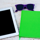 Notebook, tablet computer. And sunglasses on a wooden table Royalty Free Stock Images