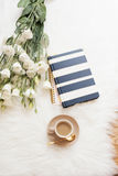 Notebook, tablet, a cup of coffee and a large bouquet white flowers on the floor on a white fur carpet. Freelance fashion comforta Royalty Free Stock Photo