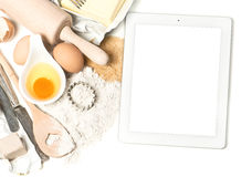 Notebook tablet pc and baking ingredients eggs, flour, yeast Stock Photo