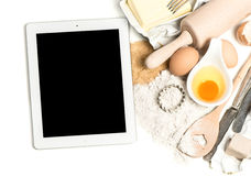 Notebook tablet pc and baking ingredients. foog background Stock Photos