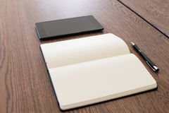 Notebook, tablet and pen on a wooden table. Work space for a journalist or blogger. Journalism activities online via social media stock photography