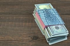 Notebook With Tear-off Sticker Pages And Dollar Cash On Wood. Notebook With Tear-off Sticker Pages And USA Dollar Cash On The Rough Brown Wood Background With Royalty Free Stock Images