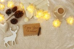 Notebook with text: ENJOY YOUR WEEKEND and cup of cappuccino over cozy and warm fur carpet. Top view Stock Photo