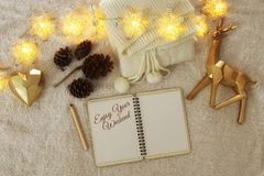 Notebook with text: ENJOY YOUR WEEKEND over cozy and warm fur carpet. Top view Royalty Free Stock Photography