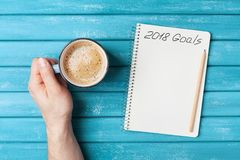 Notebook with text 2018 goals and cup of coffee on wooden desk top view. Planning and business concept. New year resolution. Notebook with text 2018 goals and stock images