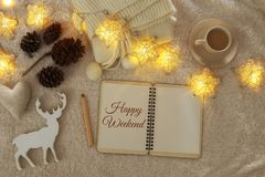Notebook with text: HAPPY WEEKEND and cup of cappuccino over cozy and warm fur carpet. Top view. Stock Photography