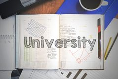 Notebook with text inside associated with the education - Univer. Sity . On table are coffee, laptop and some sheet of papers with charts and diagrams Royalty Free Stock Image