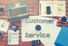 Notebook with text inside Customer Service on table with coffee,. Mobile phone and glasses Stock Photos