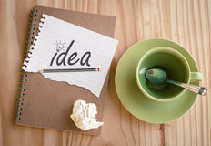 Notebook with text inside Idea and light bulb on table Stock Photo
