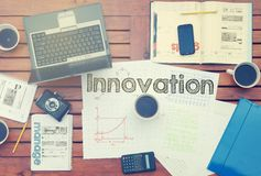 Notebook with text inside Innovation on table with coffee, some. Diagrams on paper and laptop Royalty Free Stock Photos