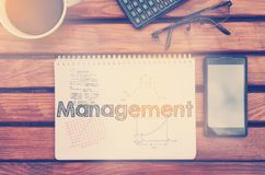 Notebook with text inside Management on table with coffee, mobil Stock Image
