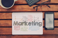 Notebook with text inside Marketing on table with coffee, mobile Royalty Free Stock Photo