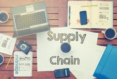 Notebook with text inside Supply Chain on table with coffee, mob. Ile phone and glasses Royalty Free Stock Images