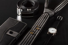 Notebook, tie, cufflinks, leather belt, watch on a black backgro Stock Photography