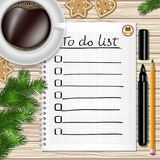 Notebook with to do list, fir tree branches, cookie, a pencil. A marker, and coffee cup on a table with wooden texture Stock Photo