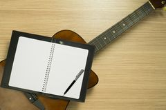 Guitar, Notebook on Wood Background. Notebook on top of an acoustic guitar on wood background. Top view Royalty Free Stock Images