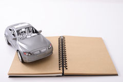 Notebook with a toy car. Blank brown notebook cover on white background Royalty Free Stock Image