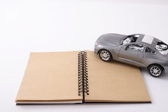 Notebook with a toy car Royalty Free Stock Photos