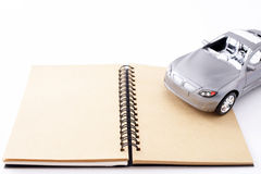Notebook with a toy car Stock Images