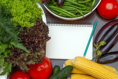 Notebook among the vegetables. Notebook for recipes on the table among the vegetables Royalty Free Stock Image