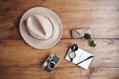 Notebook, vintage camera, compass, sunglasses and hat. Royalty Free Stock Photography