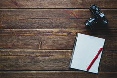 Notebook and vintage camera on the desk Stock Images