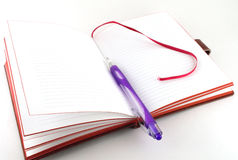 Notebook and violet pen Stock Images