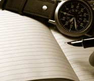 Notebook and watch. Pen notebook and watch monochrome image Stock Photos