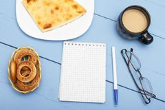 Notebook with white sheet for write and light breakfast. Cup hot tea or coffee with milk and pie. Blue wooden table Stock Photo