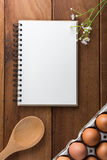 Notebook white on a wooden floor with egg. Dishes Royalty Free Stock Image