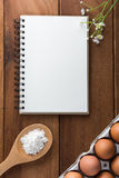 Notebook white on a wooden floor with egg. Dishes Royalty Free Stock Photography