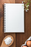 Notebook white on a wooden floor with egg. Dishes Royalty Free Stock Photos
