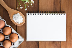 Notebook white on a wooden floor with egg. Dishes Stock Photography