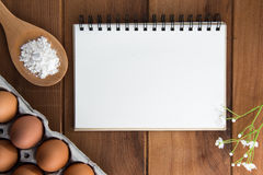 Notebook white on a wooden floor with egg. Dishes Stock Photos
