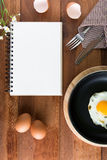 Notebook white on a wooden floor with egg. Dishes Royalty Free Stock Photo