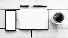 Notebook on a white wooden table next to a mobile, a pen and some coffee in a mug. Top view and empty copy space. For Editor`s text Stock Image