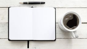 Notebook on a white wooden table next to a pen and some coffee in a mug. Top view and empty copy space. For Editor`s text Royalty Free Stock Photos