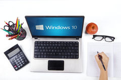 Notebook with windows 10 and student hand. JAKARTA, SEPTEMBER 03, 2015: Closeup of a notebook computer with windows 10 logo and a student hand writing on the Royalty Free Stock Image