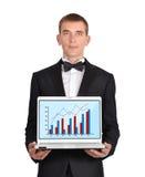 Notebook  wirth chart. Businessman in  tuxedo holding notebook  wirth chart Royalty Free Stock Images