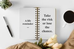 Notebook with wisdom quote and coffee cup. stock photo