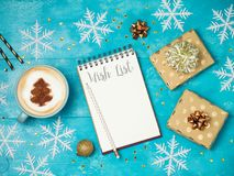 Notebook with wish list ,gift boxes and coffee cup. On wooden table.Christmas holiday background. View from above. Flat lay Stock Photos