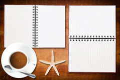 Notebook on the wood texture with coffee cup. Stock Photos