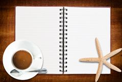 Notebook on the wood texture with coffee cup. Stock Photography