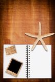Notebook on the wood texture with star fish. Stock Images