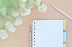 Notebook on wood with white Globe Amaranth and pencil Royalty Free Stock Images