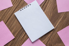 Notebook on wooden background around post-in notes. White notebook on wooden background around pink post-in notes Royalty Free Stock Images