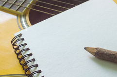 Notebook and wooden pencil on guitar. Writing music royalty free stock image