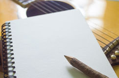 Notebook and wooden pencil on guitar. Writing music stock photos