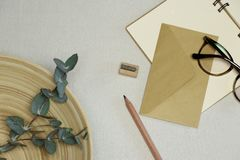 The notebook, wooden pencil & sharpener, envelope, spectacles, eucalyptus branches in the basket royalty free stock photo